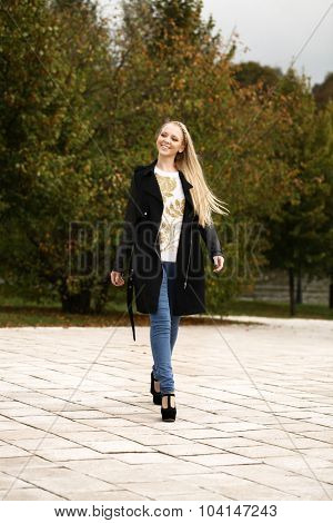 Full length, walking happy blonde woman in autumn park