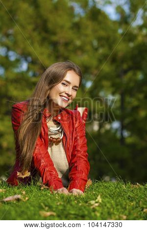 Portrait of a beautiful young woman in a red leather jacket lying on the lawn in the autumn park