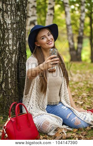 Selfie, Young beautiful blonde woman in a hat photographing themselves on a cell phone while sitting in the autumn park