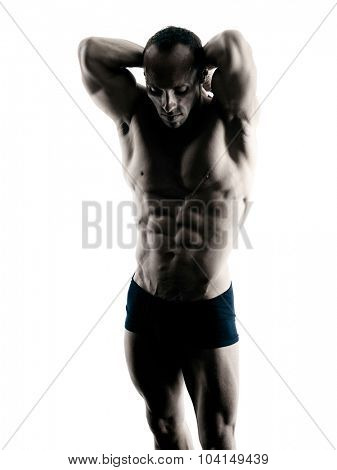 one caucasian man exercising fitness body building exercises in studio in silhouette isolated
