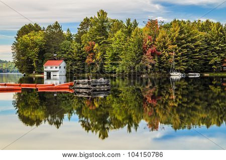 A glass like reflection of a boathouse sailboat and floats on Mary Lake in autumn.