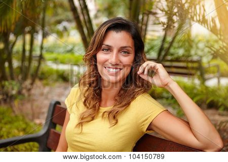 Young Woman Smiling While Sitting On Park Bench