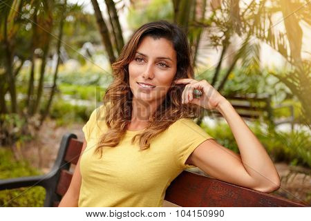 Young Woman Sitting On Bench With Hand In Hair
