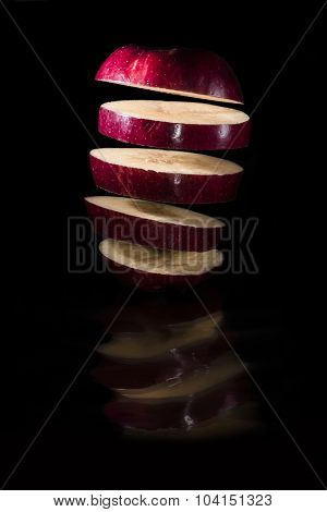 Levitating apple slices on mirror illuminated by flash.
