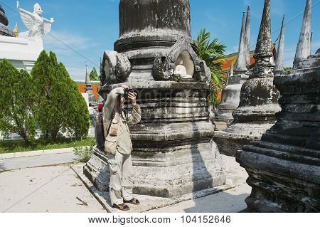 Tourist takes photo of ancient stupas in Nakhon Sri Thammarat, Thailand.