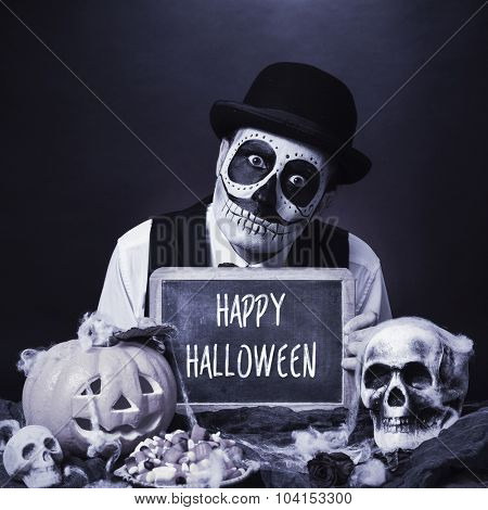 a man with calaveras makeup, wearing bowler hat, shows a chalkboard with the text happy halloween, in a dismal scene with a carved pumpkin and skulls, in black and white