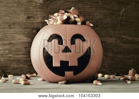 a carved pumpkin full of different halloween candies, on a rustic wooden background, with a filter effect