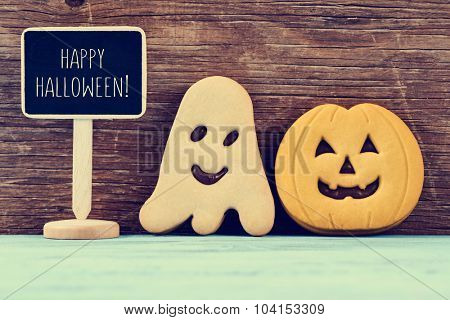 a chalkboard with the text happy halloween, a ghost-shaped cookie and a pumpkin-shaped cookie on rustic blue wooden surface