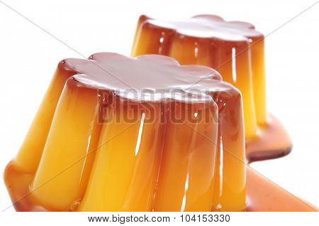 closeup of some creme caramel topped with caramel sauce on a white background