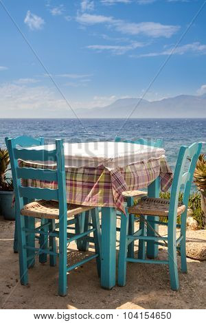 Blue wooden table with chairs of outdoor greek cafe overlooking the sea