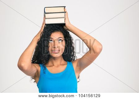 Portrait of a young afro american woman holding books on the head and looking up isolated on a white background
