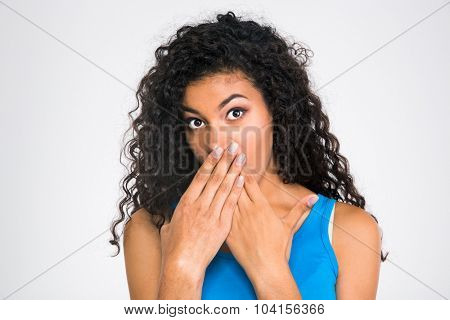 Portrait of a african woman covering her mouth isolated on a white background