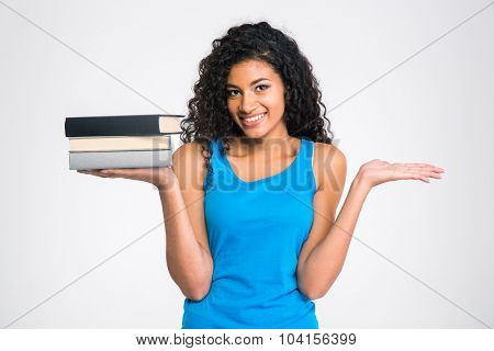 Portrait of a smiling afro american woman holding books and copyspace on the palms isolated on a white background