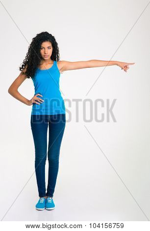 Full length portrait of a serious afro american woman pointing finger away isolated on a white background