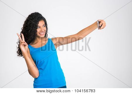 Portrait of a happy afro american woman making selfie photo isolated on a white background