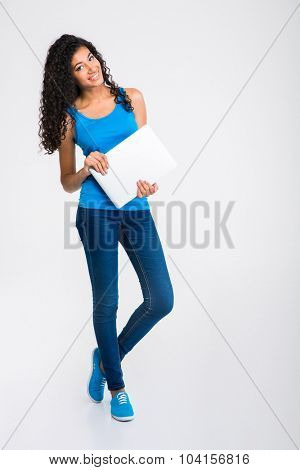 Full length portrait of a happy afro american woman holding laptop isolated on a white background