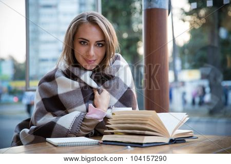 Portrait of a smiling pretty girl sitting at the table with book and coffee