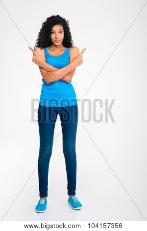 Full length portrait of a happy afro american woman pointing fingers away isolated on a white background