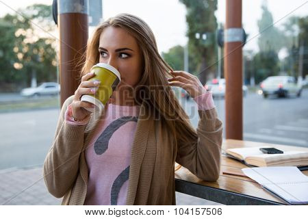 Portrait of a young girl drinking coffee in cafe