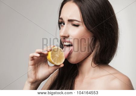 Funny Image Of Young Woman Eating Lemon