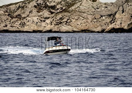 A Man At Full Speed On A Small Boat