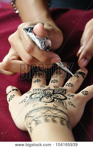 Female Henna Artist Applies A Henna Design To The Back Of A Woman's hand