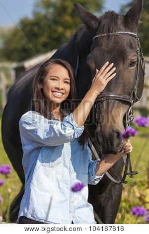 Beautiful happy Asian Eurasian young woman or girl wearing denim shirt, smiling and leading her horse in sunshine
