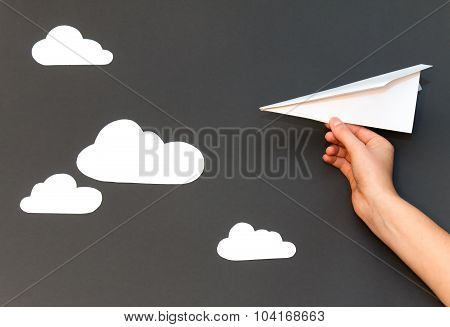 White paper airplane with clouds on a gray background
