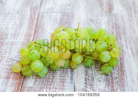Green and purple round grapes on old wooden table, selective focus