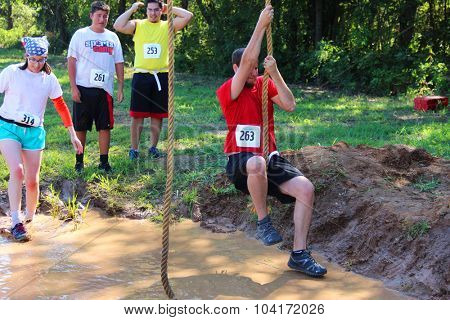 MUSKOGEE, OK - Sept. 12: A young athlete tries to avoid bloody zombies by jumping over a muddy pond during the Castle Zombie Run at the Castle of Muskogee in Muskogee, OK on September 12, 2015.
