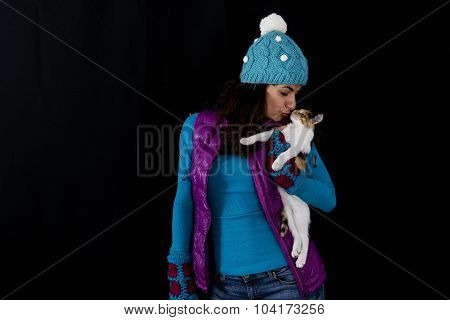 Teenage girl in winter clothes playing with her cat