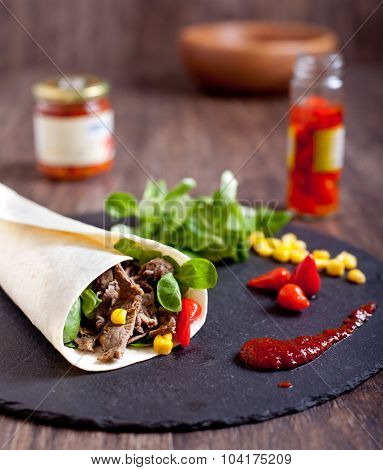 Beef fajitas roll with hot peppers, salad, corn