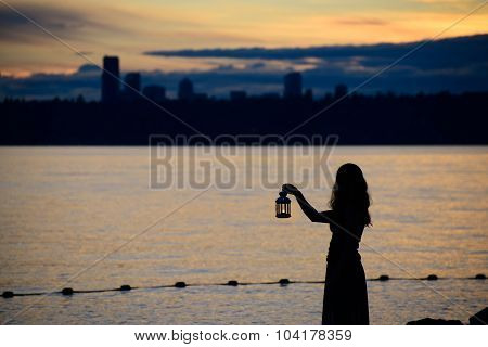 Beautiful Young Woman With Lantern Waiting On The Lake In Twilight
