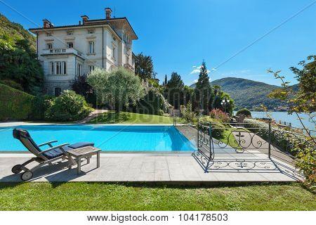 external of a villa, beautiful swimming pool overlooking the lake