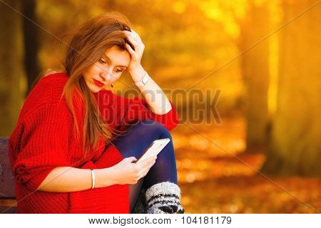 Sad Upset Girl With Mobile Phone In Autumn Park