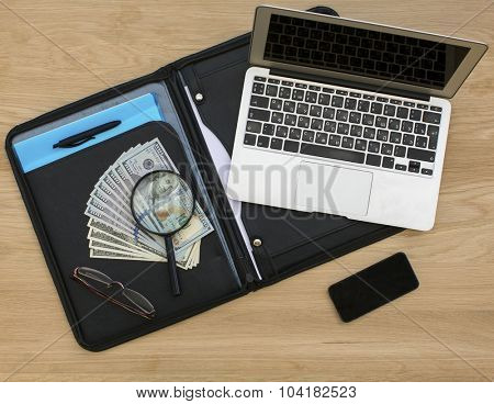 Business folder with dollar bills, opened laptop and smartphone on wooden table surface.