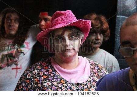 MUSKOGEE, OK - Sept. 12: A woman in a pink hat and bloodied face waits for runners at the Castle Zombie Run at the Castle of Muskogee in Muskogee, OK on September 12, 2015.