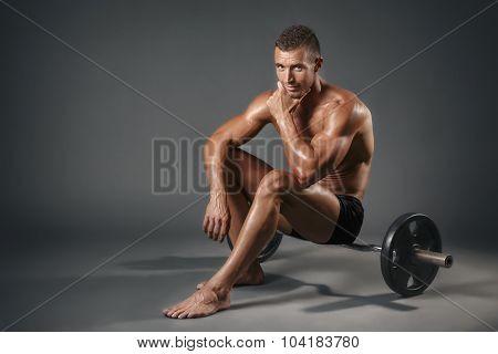 Bodybuilder sitting on 10 kg weight