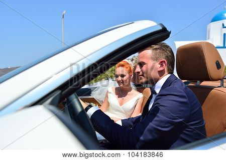 Beautiful young couple bride and groom posing in the white car on Santorini island, Greece