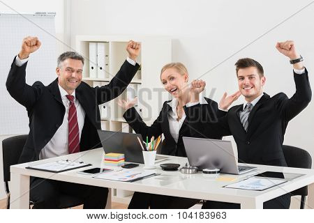 Happy Businesspeople With Arm Raised In Office