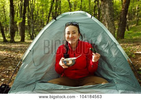 Woman with long hair has her breakfast sitting in tent