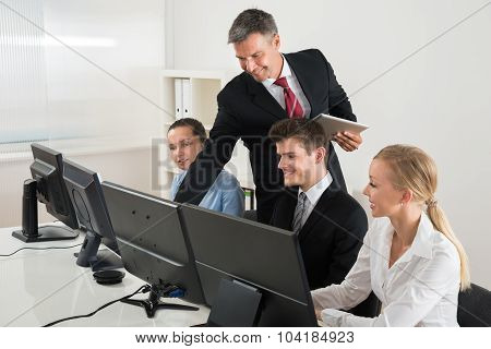 Professor Showing To Businesspeople On Computers