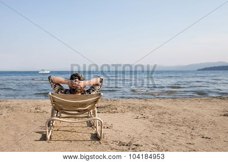 Woman In Beach Chair Looking Away At Horizon
