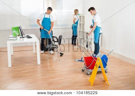 Janitors In Blue Apron Cleaning Office