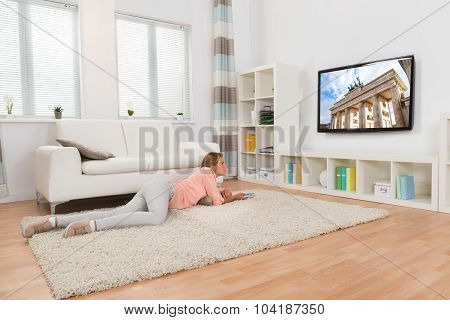 Woman Lying On Carpet While Watching Television