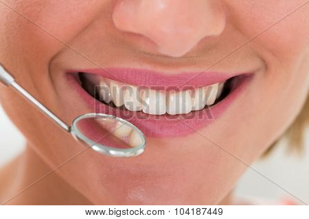 Woman With Teeth And Dentist Mirror