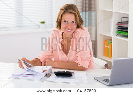 Woman Doing Calculation At Desk