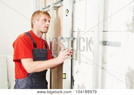 Carpenter joiner plasterer with screwdriver mounting gypsum plasterboard framework system on wall