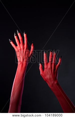 Red devilish hands with black nails, Halloween theme, studio shot on black background