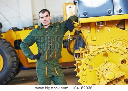 industrial worker during heavy industry machinery bulldozer assembling on production line manufacturing workshop at factory